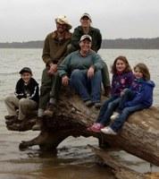 Family sitting on log at lake's edge
