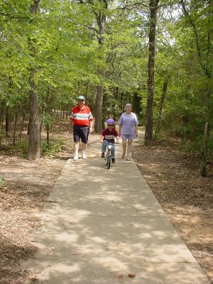 Two adults walking and child riding bike on paved trail.