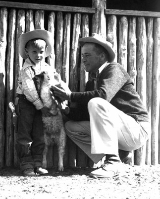 Rancher and small boy holding an animal