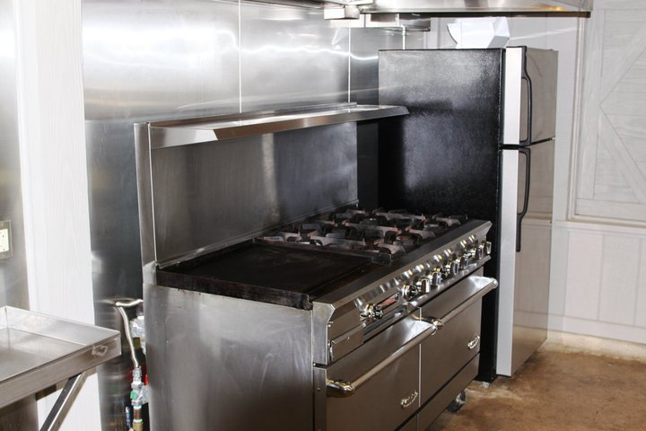 There is a commercial stove/oven, vent hood with fire suppression system, refrigerator, freezer, and microwave.