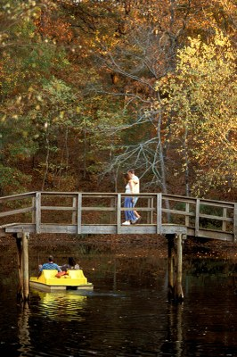 Couple strolling on bridge with pedal boat underneath.