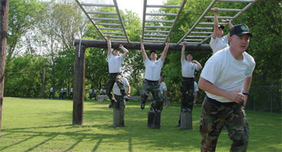 Numerous cadets on monkey bars of obstacle course