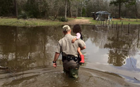 Game Warden carries a small child out of loodwaters