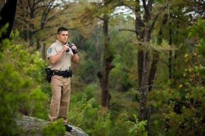 Game Warden in the woods holding binoculars