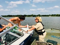 Game Warden checking a fire extinguisher on a boat