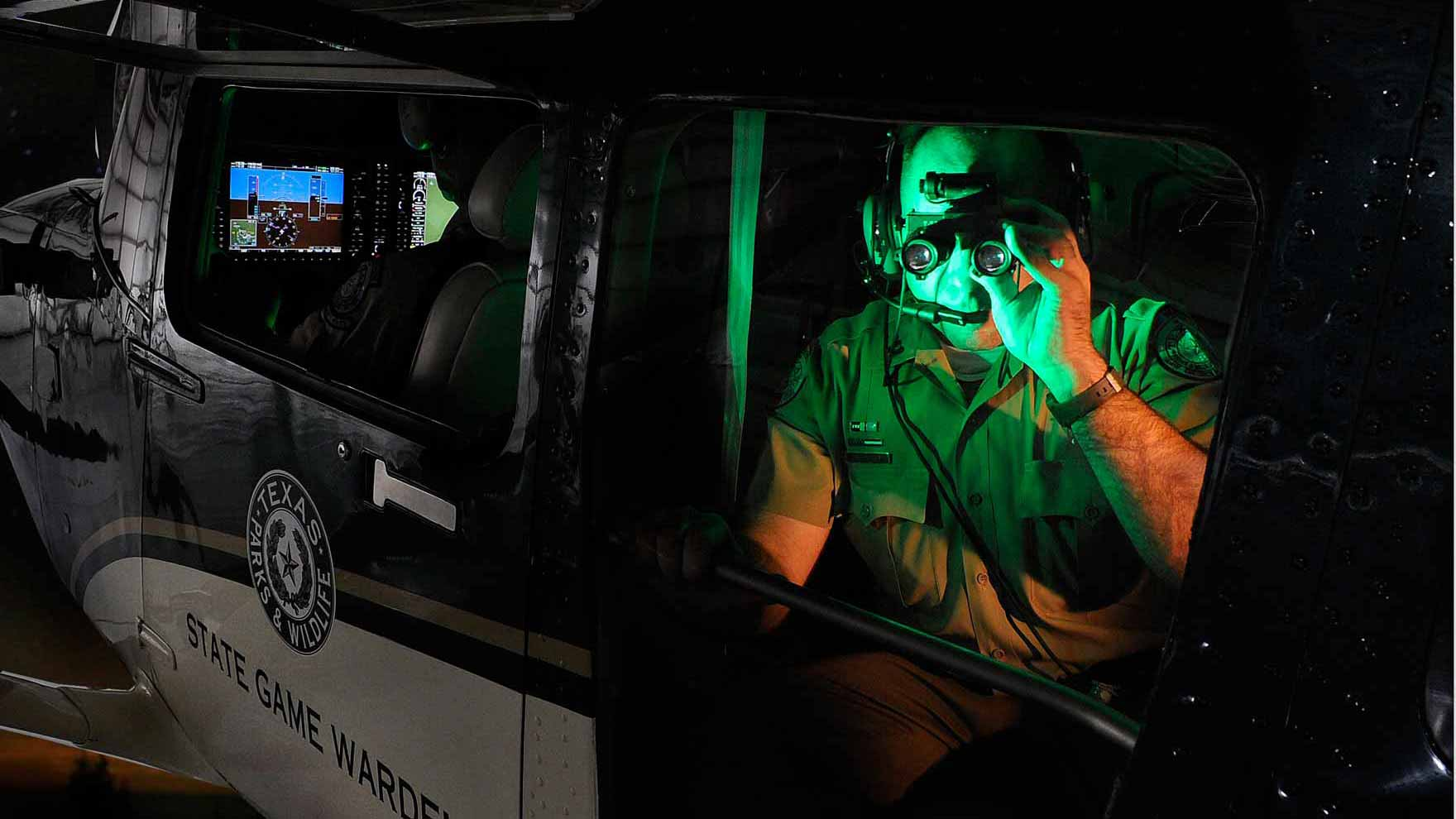 Game Warden using night vision goggles from fixed wing aircraft at night