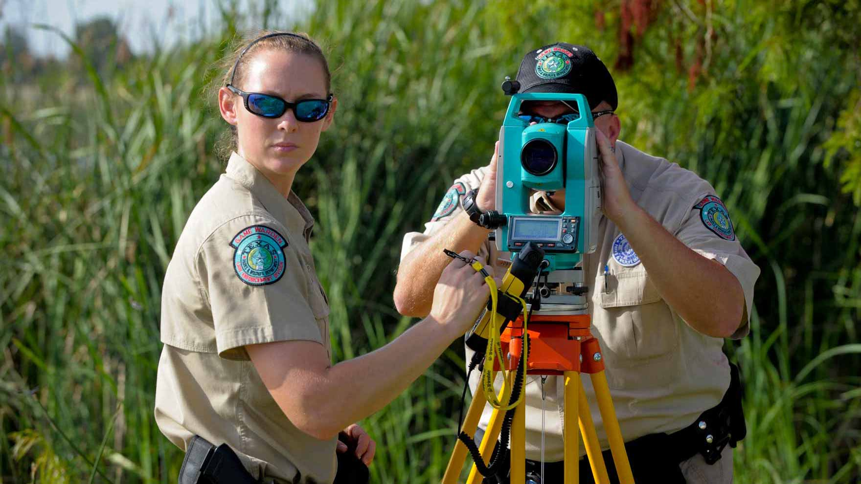 Two Game Wardens using a laser mapping device to plot a boating accident