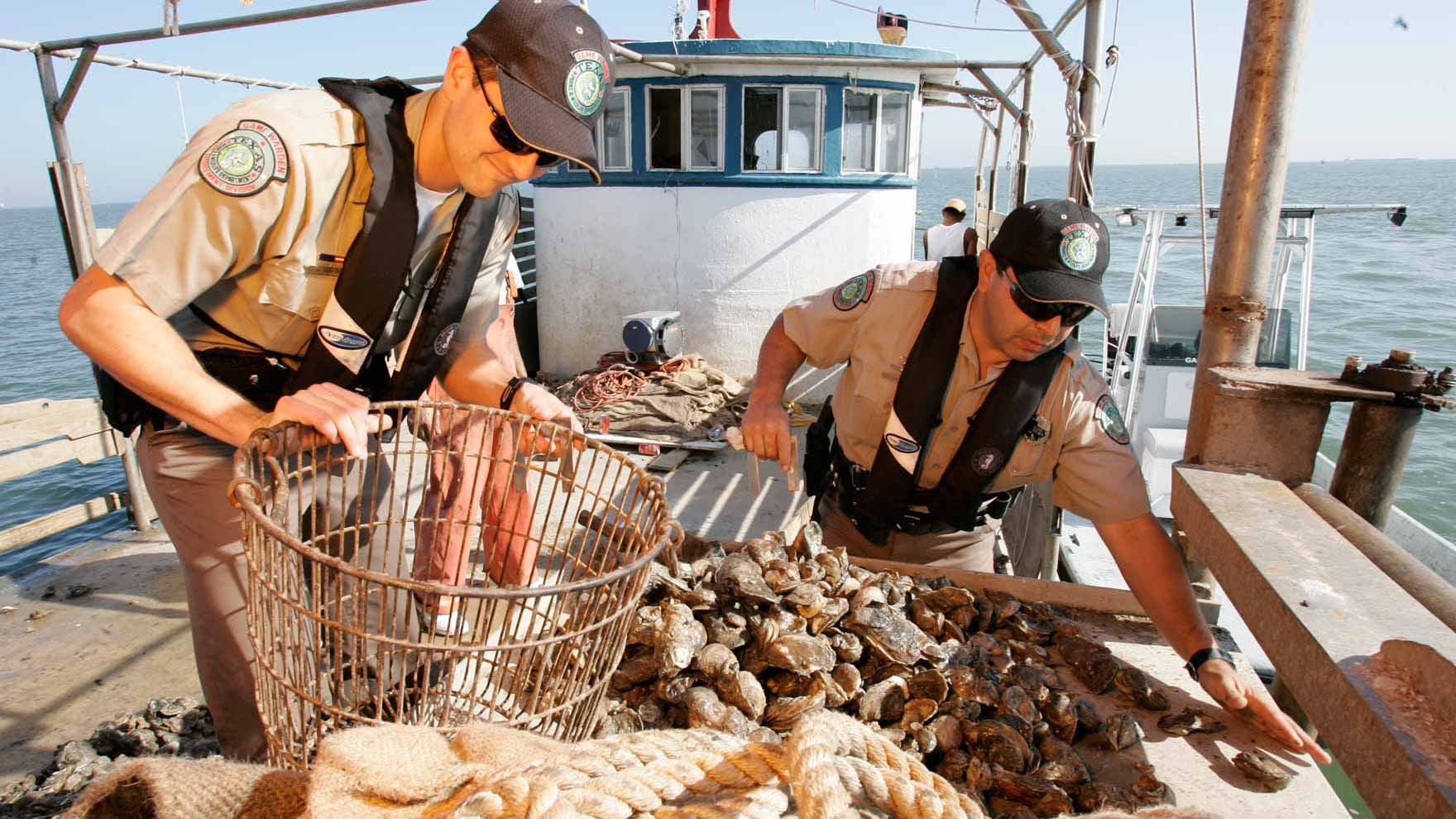 Two Game Wardens checking an oyster boat harvest in Galveston Bay
